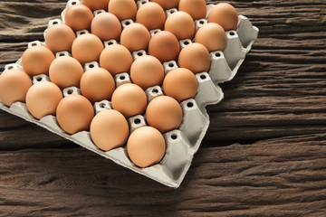 aw chicken eggs in egg box on old brown wooden