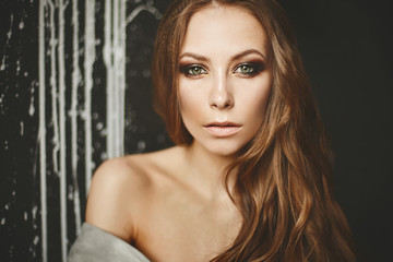 Portrait of beautiful fashionable brown-haired girl with green eyes and professional make-up