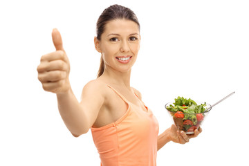 Young woman with a salad making a thumb up sign