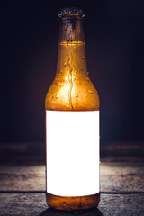 Bottle of beer with blank label on the wooden background