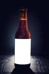 Blank label on the beer bottle on dark background