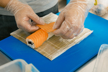 Professional sushi chef preparing roll at commercial kitchen. Cook puts the salmon on roll. Japanese cuisine recipes