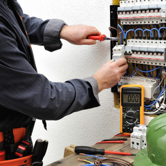 Elegant electrician technician at work on a residential electric panel