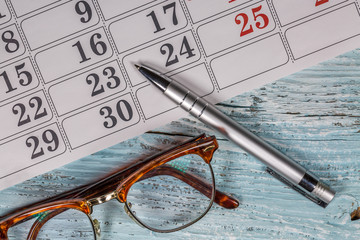 Eyeglasses,Calendar And Pen On Wood
