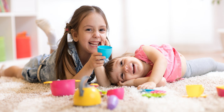 Cute funny children playing with dishware toys at home