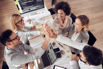 Happy business team giving high five in office