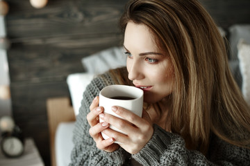 Cheerful woman drinking morning coffee.