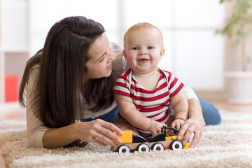 cute mother and child boy play together with toys indoors at home