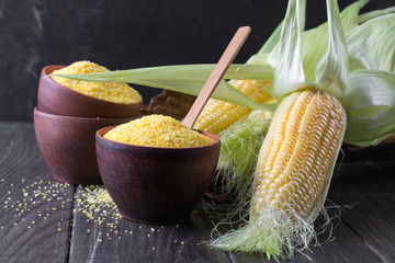 Ripe raw corn cob and green leaves on dark wooden background. Corn grits polenta in a  ceramic bowl