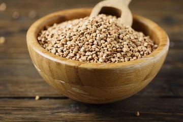 Raw buckwheat grain on the wooden table