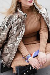 Fashion blogger wearing beige dress and bomber jacket