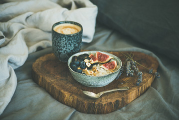 Healthy winter breakfast in bed. Rice coconut porridge with figs, berries and hazelnuts and cup of coffee over rustic wooden board background. Clean eating, alkiline diet, vegan food concept