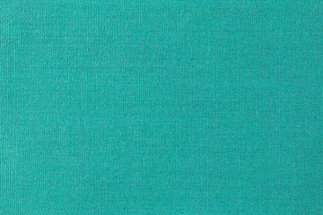 Close view of old green fabric with a close weave.