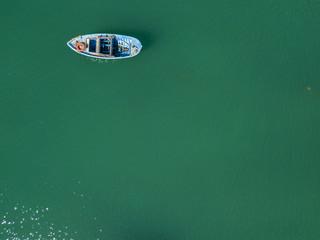 Vista aerea di una barca a remi che galleggia sul mare verde