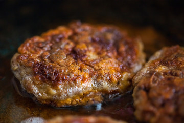 Steaks in a frying pan are roasted on the stove. Fried cutlets