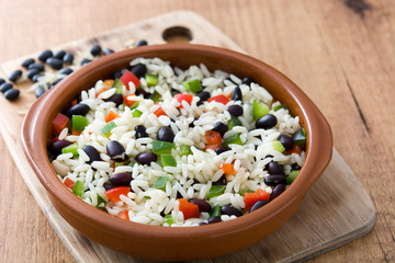 Traditional cuban rice, black beans and pepper on wooden table background. Moros y cristianos.