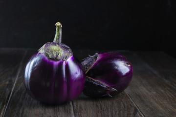 Raw  purple round eggplants on dark rustic wooden background.