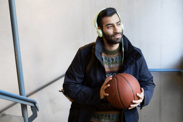 Adult man with beard and headphones holding basketball