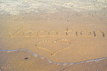 Vacation written in the sand.