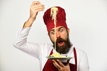 Cook with shocked face in uniform holds fork and plate.