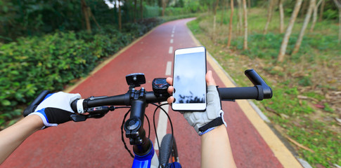 Cyclist using smartphone for navigation when riding mountain bike on forest trail ... .