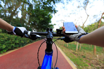 Cyclist using smartphone for navigation when riding mountain bike on forest trail