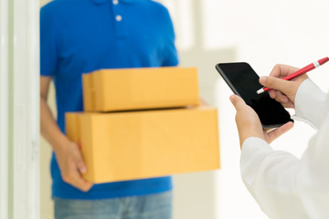 Woman receiving package and signing on digital mobile phone from delivery man.