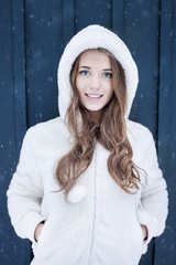 Portrait of young long-haired woman wearing white fluffy hoodie