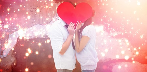 Composite image of couple covering their kiss with a heart