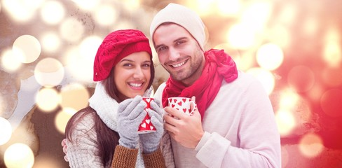 Composite image of winter couple holding mugs
