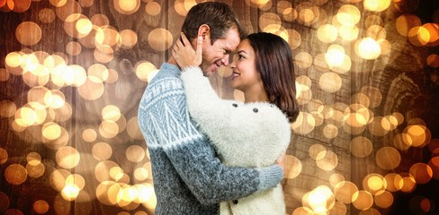 Composite image of couple wearing warm clothing embracing