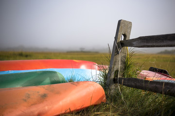 Boats on field by wooden fence against sky