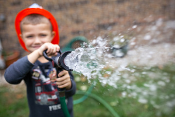 Boy wearing helmet while spraying water with garden hose at backyard