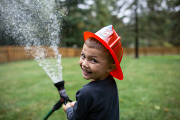 Boy in red helmet spraying water in garden