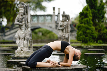 Woman practicing yoga on a platform amidst pond in the park