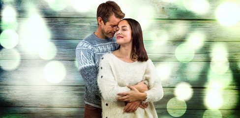 Composite image of romantic couple in warm clothing