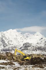 Excavator working near mountains in winter