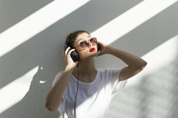 Woman wearing sunglasses listening music while standing against white wall