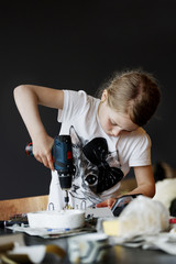 Young girl working with drill in workshop
