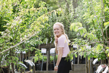 Smiling woman standing among trees ready to plant