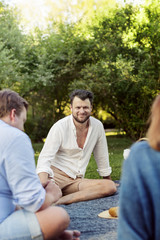 Smiling bearded man sitting with friends at picnic