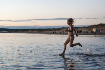 Young girl running in shallow water