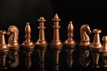 gold chess pieces on a black glossy