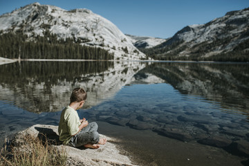 Side view of boy sitting on rock by lake against mountains at Yosemite National Park