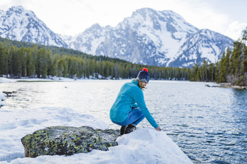 Full length of woman crouching on rock amidst frozen lake against mountains