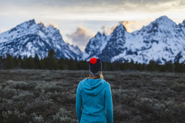 Woman looking at view while standing on field against mountains during winter