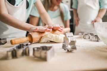 Happy family shape the dough for baking closeup