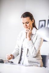 Thoughtful young businesswoman working at office desk