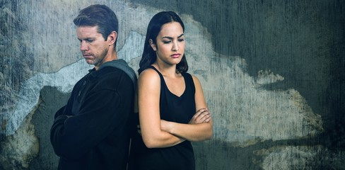 Composite image of sad couple with arms crossed standing back to