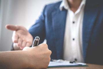 Business man hand is inviting partner to sign the agreement business deal